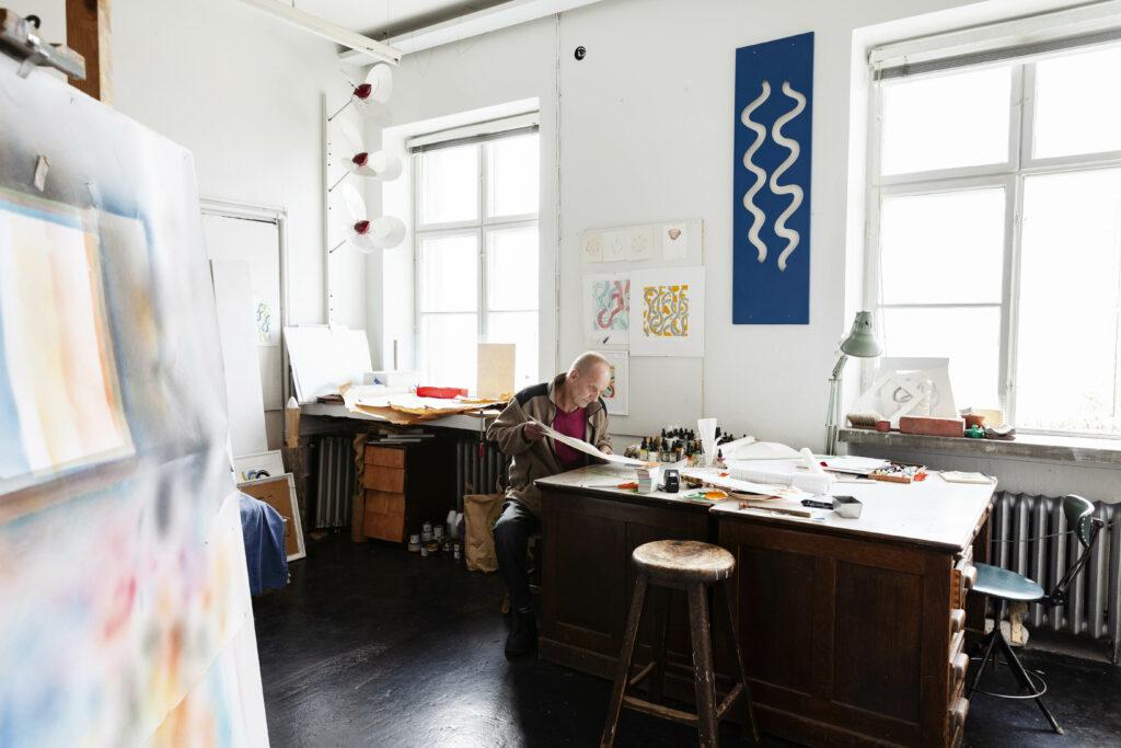 Taiteilija valoisan työhuoneensa työpöydän ääressä.