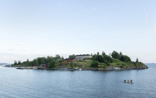 Harakan saari kesäillassa. Saaren laella häämöttää Taiteilijatalo, merta, etualalla soutajat